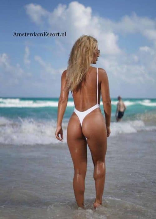 Franzi standing on beach in white bathing suit with butt facing.