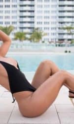 Franzi laying by pool in black bathing suit.