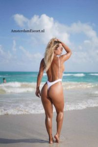 Franzi walking on beach in white bathing suit with hand in her hair.