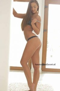Amirah Standing Topless in Black G-String from Her Side.
