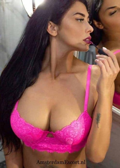 Caprise Applying Lipstick While in Pink Panties and Top.