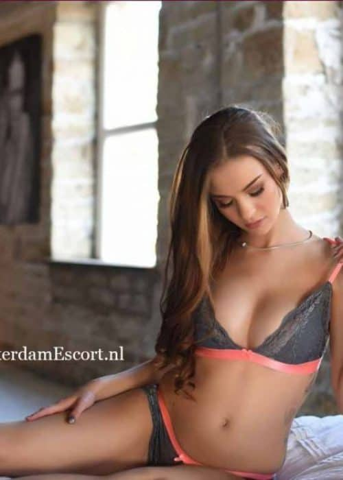 Emelia Kneeling Topless in Black Lingerie Holding Right Breasts.