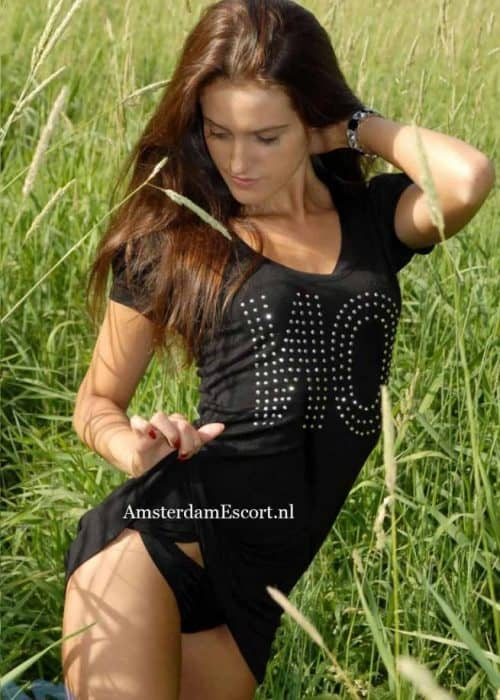 Flora Standing in Field Outside with Black Shirt and Panties with Hand Behind Back.