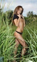 Flora Standing in Field Outside Pulling Up Black Shirt in Black Panties on Her Side.