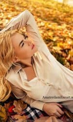 Manuela Laying on Ground with Leaves Around Her While Hands Behind Head.