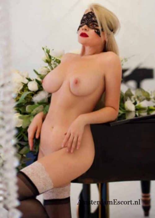 Manuela Standing Fulling Nude Against Piano with Black Mask and Hands on Her Side.