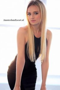 Morena Standing in Black Dress with Long Blonde Hair Hanging Down.