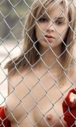 Phoebe Standing Behind Chain Link Fence with Red Top Open Showing Breasts.