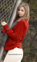 Phoebe Standing Against Chain Link Fence in Red Top and White Skirt.