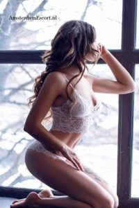 Rosa Squatting on Knees in White Lingerie Looking Out of Window.