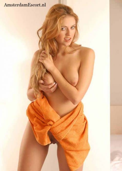 Samantha Holding Breasts With Orange Towel At Waist.