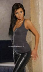 Viona standing In Black Leather Pants Against The Wall.
