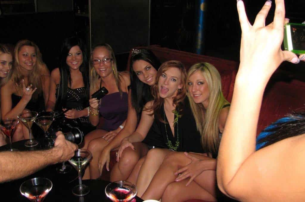 Photo of Several Girls Sitting Around Dance Stripper Services Pole.