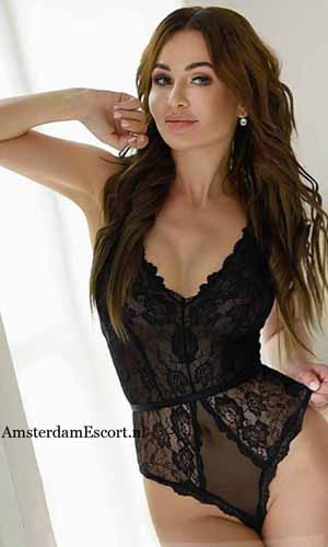 Cassidy standing in black lingerie with hand on her head.